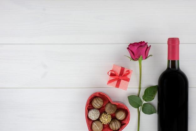 Decoração romântica do dia de valentim com rosas, vinho e chocolate em uma tabela de madeira branca.