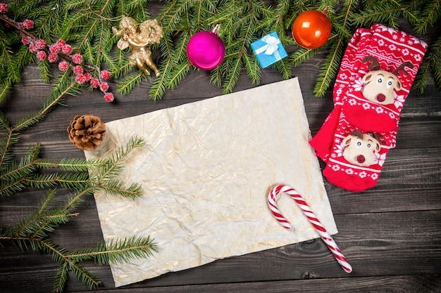 Decorações, anjo, pirulito, meias de cone e natal emolduram um papel velho