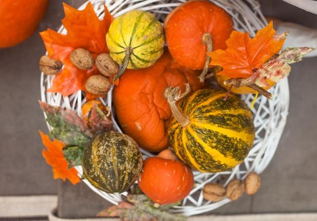 Decorações ao ar livre de outono ou outono com pimpkins e folhas na cesta