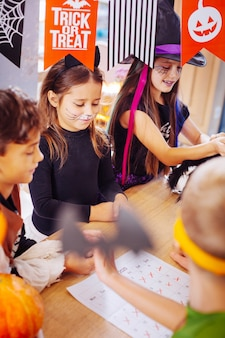 Decorações brilhantes. crianças bonitas e fofas com rostos pintados desfrutando de incríveis decorações brilhantes na festa de halloween Foto Premium