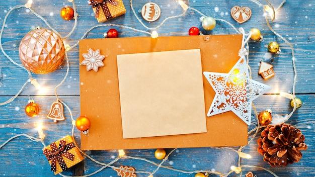 Decorações de ano novo em torno do espaço vazio de carta de natal para texto queimando guirlandas de luzes sobre fundo azul de madeira.