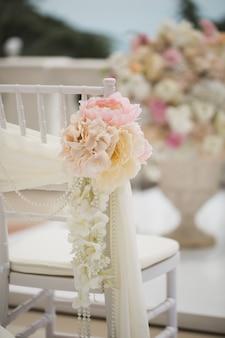 Decorações de casamento flores em cadeiras. registro de saída do casamento, cadeiras brancas decoradas para o casamento. detalhes de configuração do casamento.