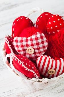 Decorações de dia dos namorados: corações vermelhos de têxteis em uma cesta branca na mesa surrada