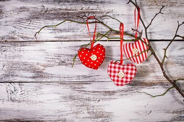 Decorações de dia dos namorados: corações vermelhos de têxteis no galho