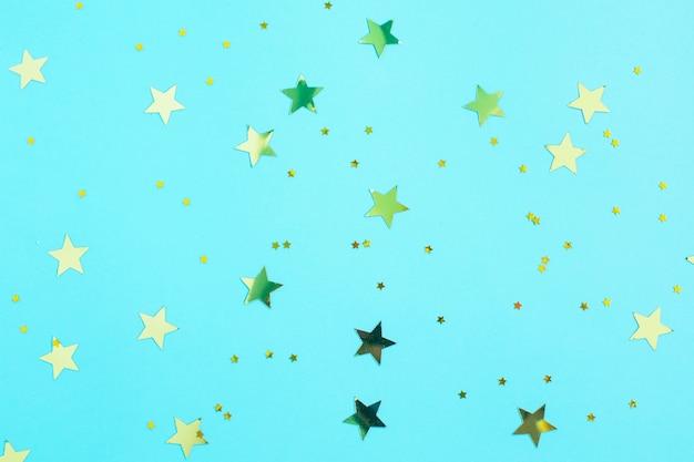 Decorações de estrelas de glitter dourados em fundo azul