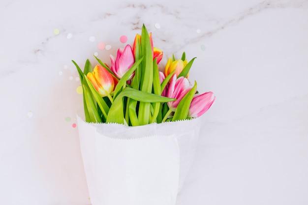 Decorações de estrelas douradas, confetes e tulipas cor de rosa e vermelhas sobre fundo de mármore