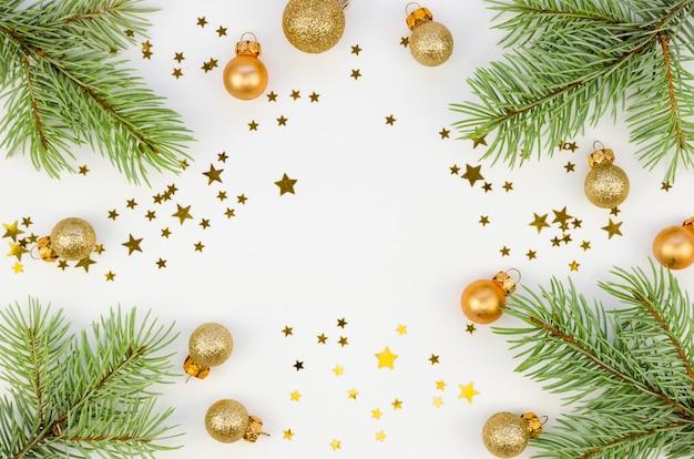 Decorações de estrelas douradas do copyspace do natal com ramos de abeto no fundo branco