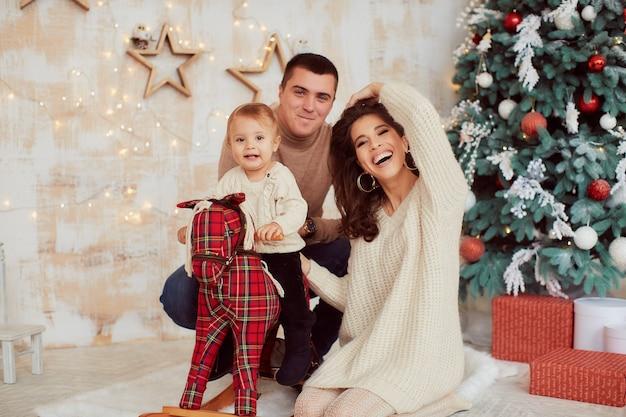 Decorações de férias de inverno. cores quentes. retrato de família. mãe, pai e sua filhinha