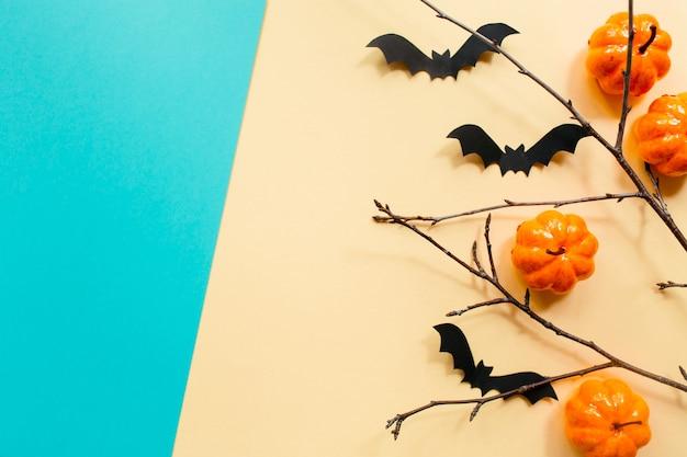 Decorações de halloween com abóbora, morcegos e galhos em fundo azul bege pastel.