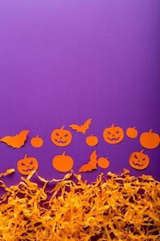 Decorações de halloween com abóboras, aranhas, morcegos, jack o'lantern de papel no fundo roxo. conceito de feliz dia das bruxas com espaço de cópia.