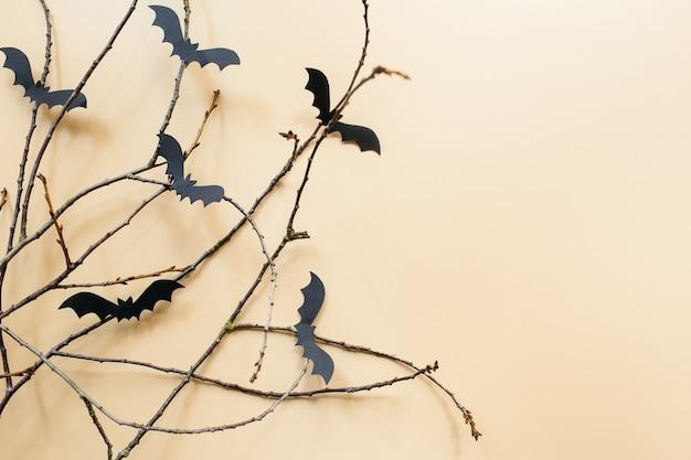 Decorações de halloween com morcegos e galhos em fundo bege pastel conceito de halloween plana leigos
