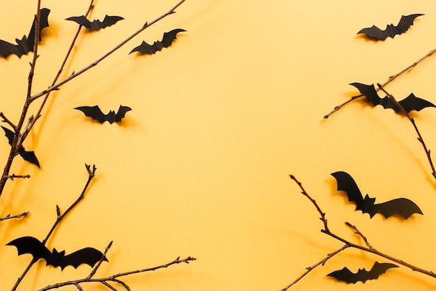 Decorações de halloween com morcegos e galhos em fundo laranja conceito de halloween plana lay top