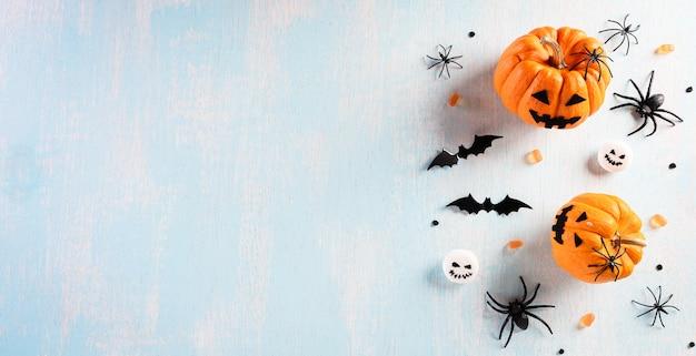 Decorações de halloween feitas de abóbora, morcegos de papel e aranha negra