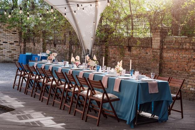 Decorações de mesa de flores para férias e jantar de casamento. mesa posta para recepção de casamento de férias no restaurante ao ar livre.