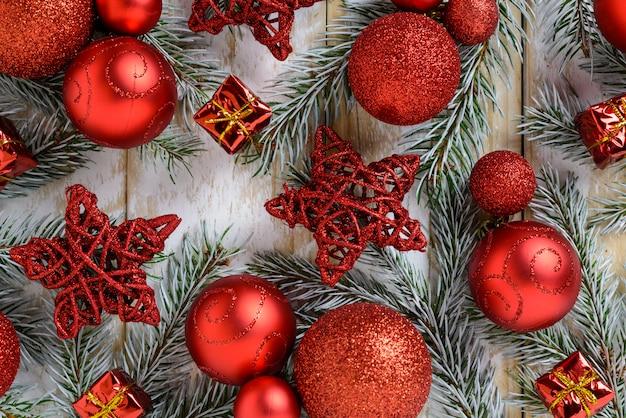 Decorações de natal, bolas vermelhas e estrelas em uma mesa de madeira branca. vista superior, copie o espaço.