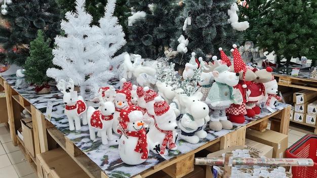 Decorações de natal, bonecos de neve com cachorros, veados, vendem em um balcão do mercado. compras de ano novo