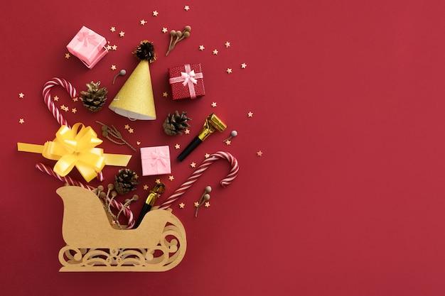 Decorações de natal brilhantes e o trenó do papai noel sobre fundo vermelho. conceito de compras e presentes. conceito de compras de natal. camada plana, vista superior