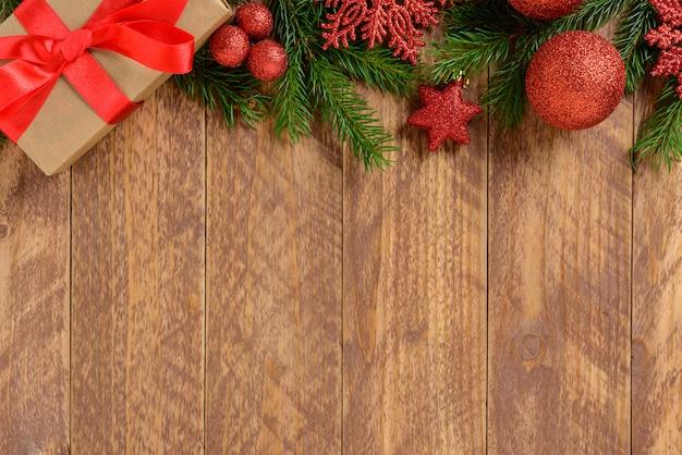 Decorações de natal, caixa de presente e bolas vermelhas em uma mesa de madeira marrom. vista superior, copie o espaço.