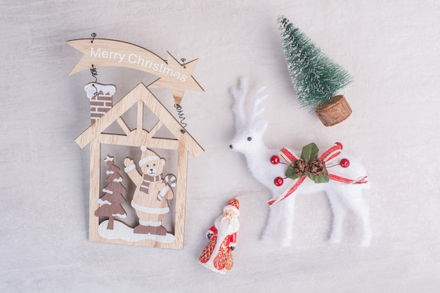 Decorações de natal, cervo de brinquedo, pinheiro e papai noel na superfície branca.