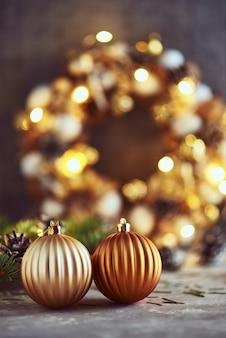 Decorações de natal com bolas douradas, galho de árvore do abeto e luzes de festão