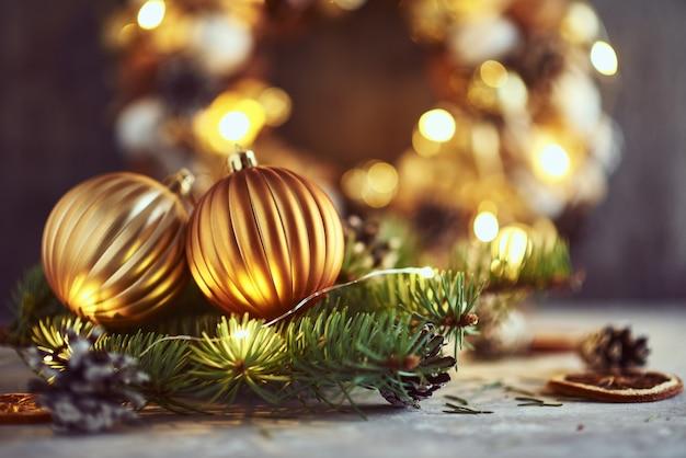 Decorações de natal com bolas douradas, galho de árvore do abeto e luzes de guirlanda