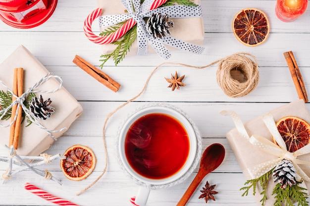 Decorações de natal com caixas de presente, pinhas e xícara de chá em um fundo branco de madeira