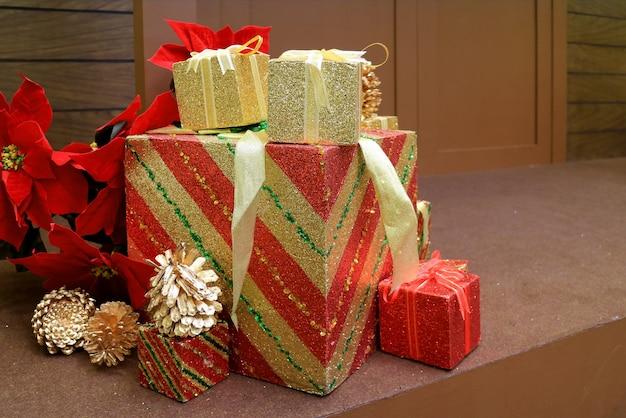 Decorações de natal com uma pilha de caixas de presente grandes e pequenas e pinhas secas no chão