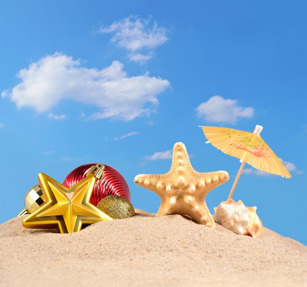 Decorações de natal, conchas e estrelas do mar na areia da praia contra o céu azul