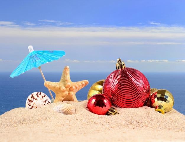 Decorações de natal, conchas e estrelas do mar na areia da praia contra o fundo do mar
