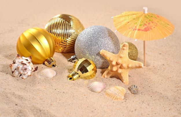 Decorações de natal, conchas e estrelas do mar na areia da praia