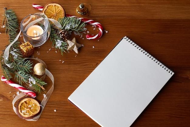 Decorações de natal douradas, chapéu de papai noel e um caderno em branco aberto