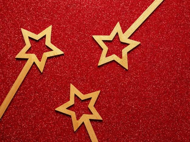 Decorações de natal douradas de madeira sobre fundo vermelho glitter vermelho. tema de natal de férias de inverno