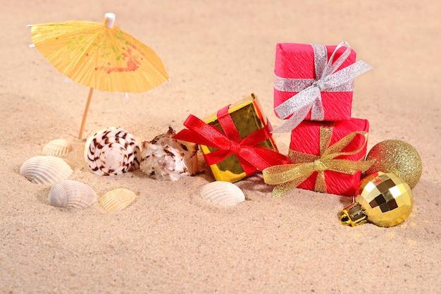 Decorações de natal e conchas na areia da praia