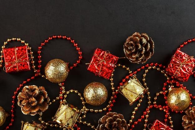 Decorações de natal em ouro e vermelho sobre um fundo preto com espaço livre. vista de cima. espírito de natal.
