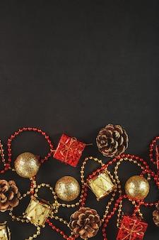 Decorações de natal em ouro e vermelho sobre um fundo preto com espaço livre. vista de cima.
