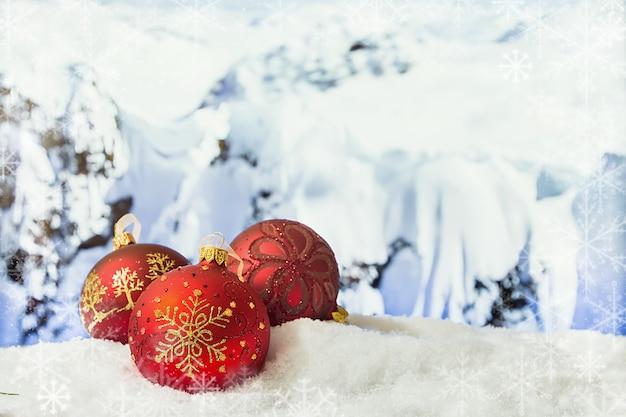 Decorações de natal em um monte de neve na frente de montanhas nevadas inverno natal superfície