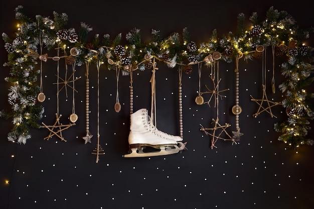 Decorações de natal em uma parede escura, feliz feriado. a parede é decorada com uma guirlanda com galhos de árvores comestíveis e patins brancos. expectativas de inverno.