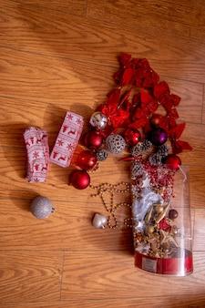 Decorações de natal espalhadas no chão de madeira da caixa.