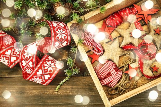Decorações de natal, estrelas de madeira e fitas vermelhas. estilo vintage com tons de luzes