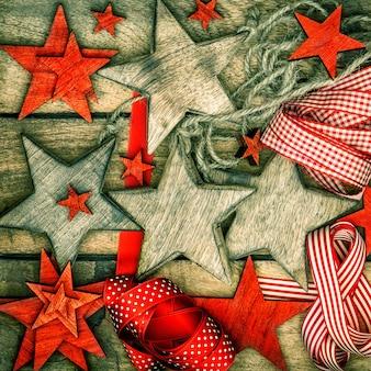 Decorações de natal, estrelas de madeira e fitas vermelhas. imagem nostálgica do estilo retro. foto escura projetada