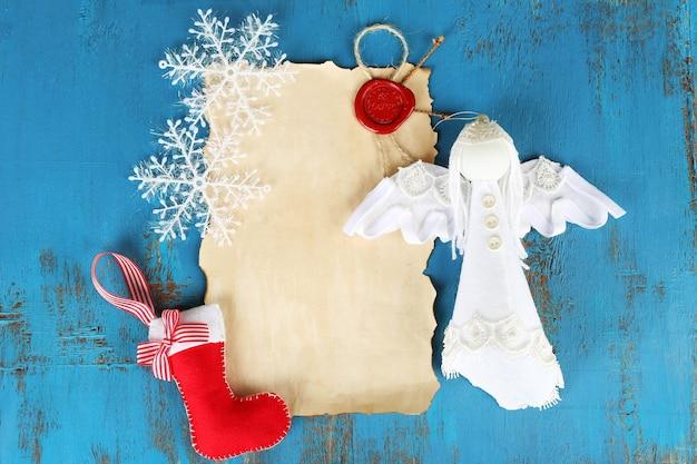 Decorações de natal feitas à mão e folha de papel velha com fundo de madeira