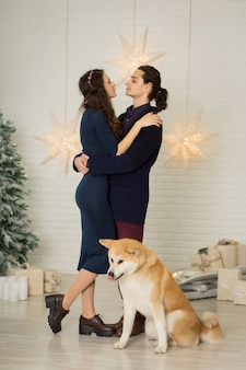 Decorações de natal. jovem casal feliz, abraçando e beijando enquanto está sentado em um banco ao lado de um cachorro
