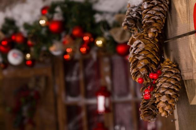 Decorações de natal macro marrom pinha com cerejas vermelhas penduradas na parede de madeira dentro da casa.