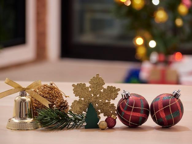 Decorações de natal na mesa de madeira com árvore de natal decorada turva e luzes de bokeh no fundo.
