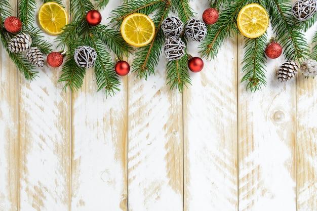 Decorações de natal, pinhas e frutas laranja em uma mesa de madeira branca. vista superior, copie o espaço.