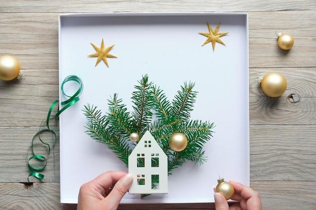 Decorações de natal planas com as mãos fazendo uma caixa decorada com a silhueta da casa, galhos de pinheiro e bugigangas douradas, bugigangas. postura plana em placas de madeira.