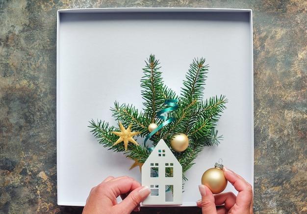 Decorações de natal planas com mãos fazendo uma caixa decorada com casa, galhos de pinheiro e bugigangas douradas, bugigangas. postura plana na mesa de madeira.
