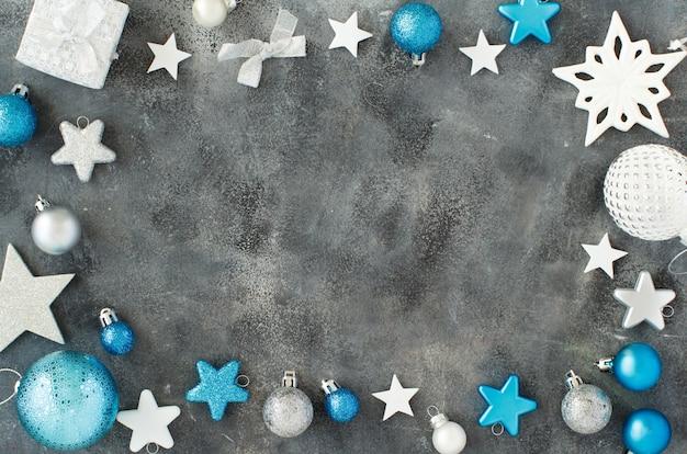 Decorações de natal prateadas e turquesas em um fundo cinza