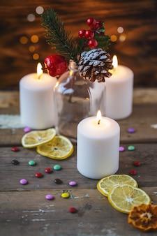 Decorações de natal, velas, doces, frutas cítricas, enfeitar um fundo de madeira. novos anos . cartão postal