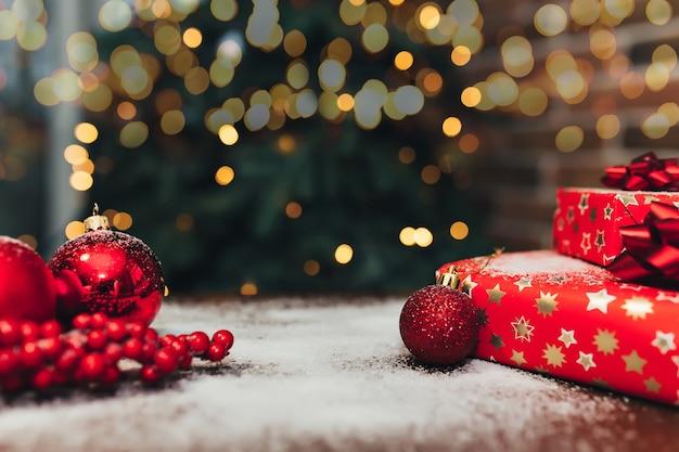 Decorações de natal vermelhas e presentes na mesa, luzes desfocadas.